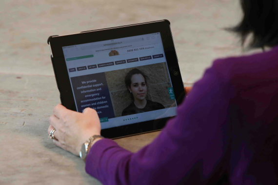 Woman looking at domestic violence website on ipad